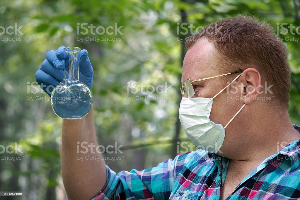 man wearing glasses, mask and gloves holding  retort stock photo