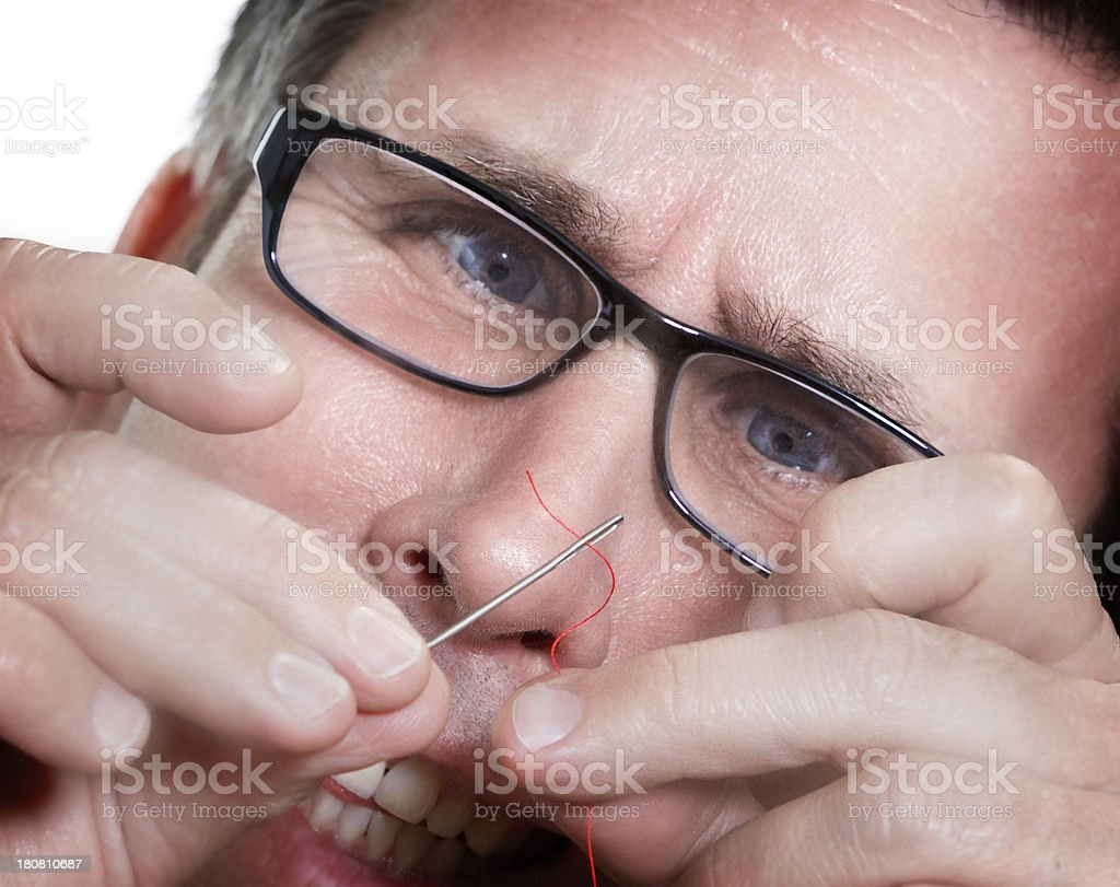 Man wearing glasses threading a needle. stock photo
