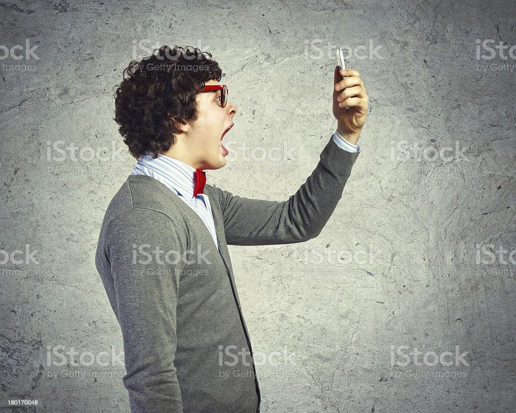 A man wearing glasses yelling at his phone stock photo