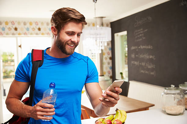 man wearing gym gear holding a bottle of water in a kitchen - day in the life series stock pictures, royalty-free photos & images