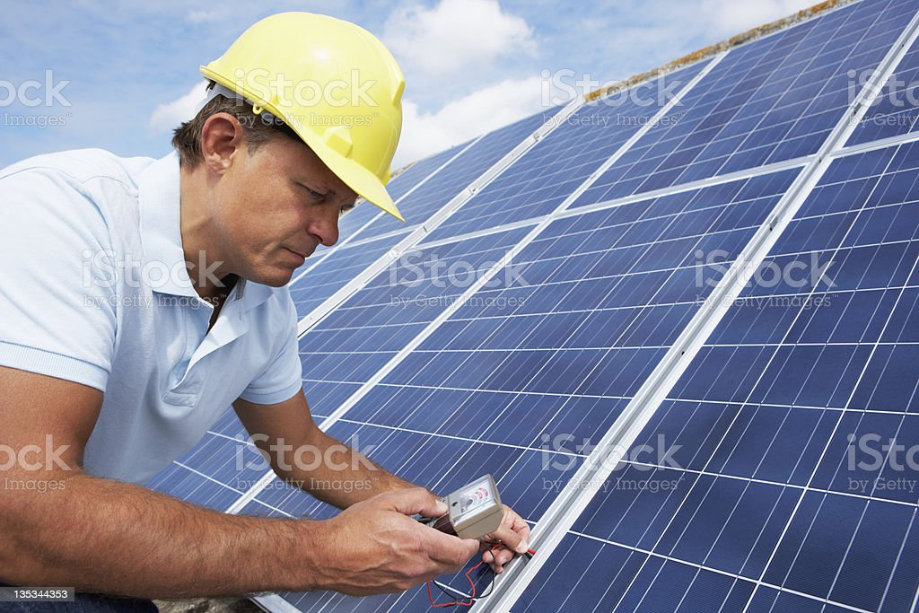 Man wearing hard hat checking roof solar panels stock photo