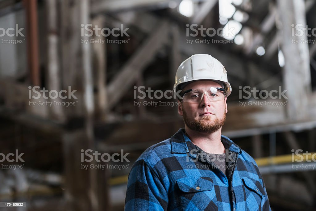 Man wearing hardhat, safety goggles and plaid shirt stock photo