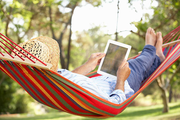 man wearing hat relaxing in hammock with e-book - hangmat stockfoto's en -beelden