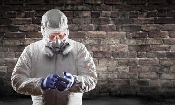 Mann trägt Hazmat Anzug, Schutzgasmaske und Brille gegen Ziegelwand – Foto