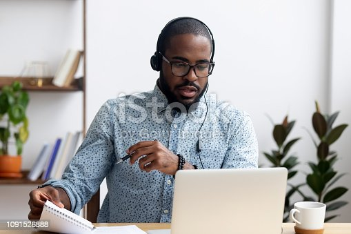 Black young man sitting at table wearing headphones learn foreign language improves knowledge looking at pc screen listening audio lesson holding pen and notepad makes some notes. E-learning concept
