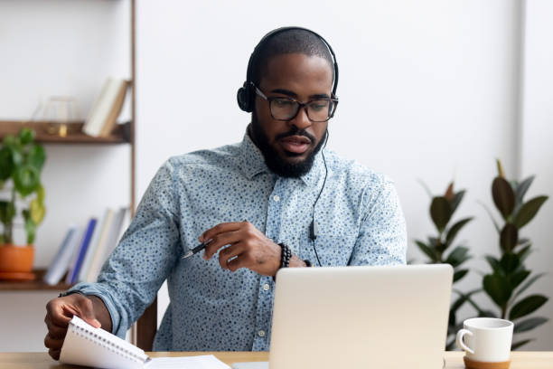 Man wearing headphones learn foreign language indoors Black young man sitting at table wearing headphones learn foreign language improves knowledge looking at pc screen listening audio lesson holding pen and notepad makes some notes. E-learning concept practicing stock pictures, royalty-free photos & images