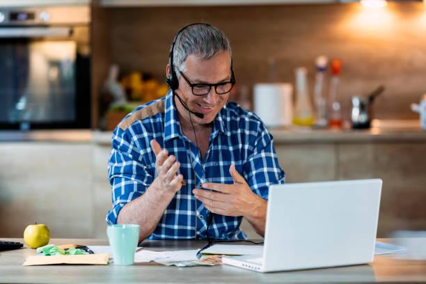 Homme utilisant des écouteurs, apprenant la langue étrangère à l'intérieur - Photo