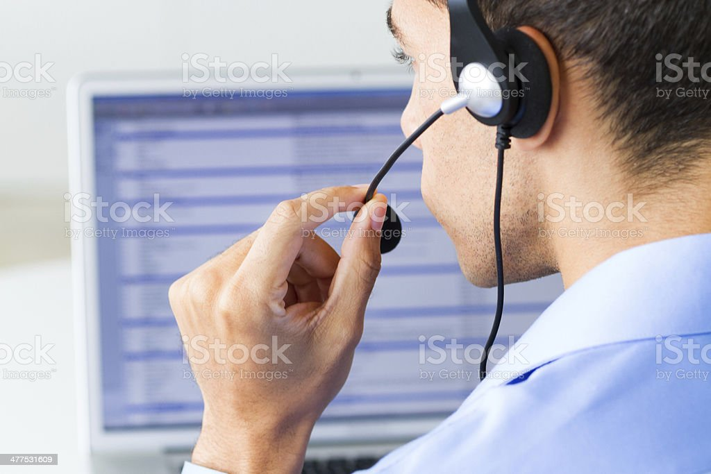 man wearing headset looking at monitor stock photo