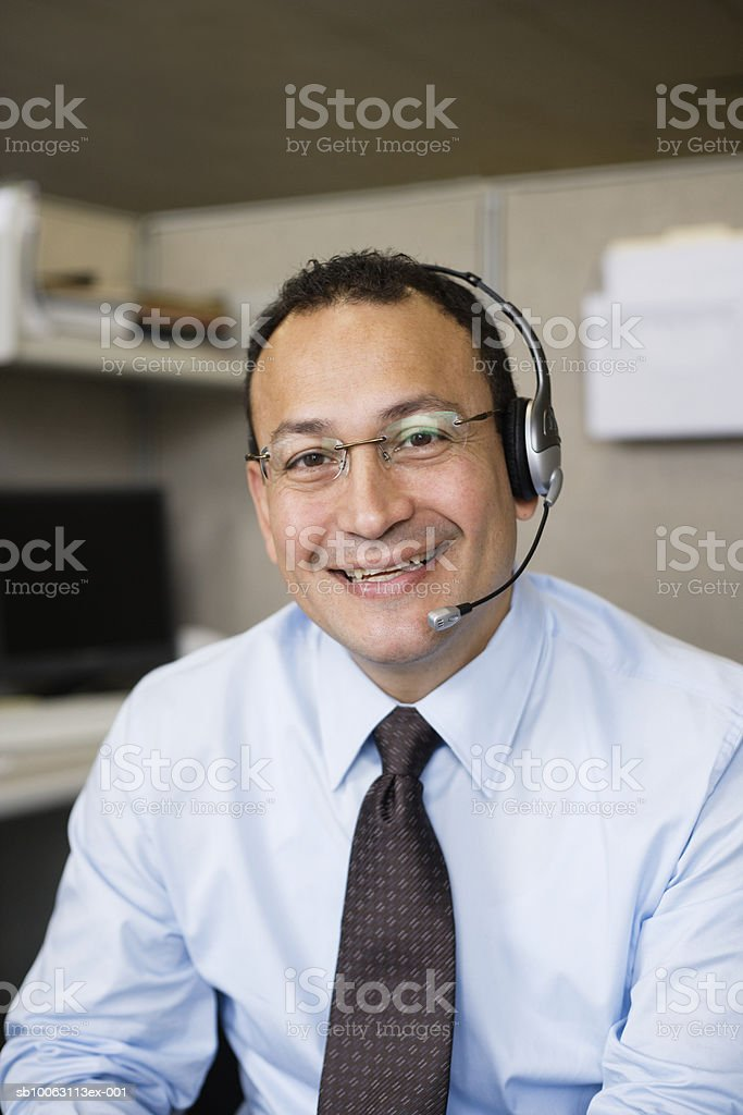 Man wearing headset, smiling, portrait, close-up royalty free stockfoto