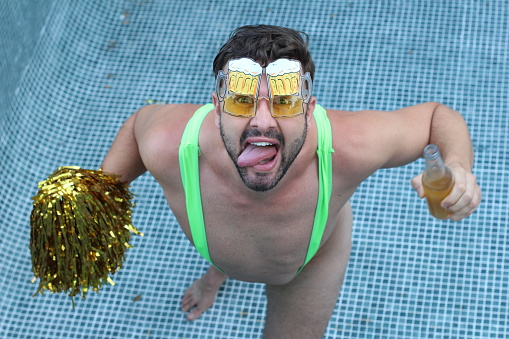 istock Man wearing hilarious outfit at pool party 1257178418