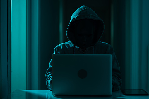Photo of adult man wearing gloves, a gray hooded sweater to hide his identity and using computer for hacking.The background is dark and atmosphere is futuristic. He is using a laptop computer.