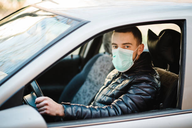 Man wearing in the medical protective mask protect from bacteria Corona virus while driving a car. Coronavirus, disease, infection, quarantine, covid-19.