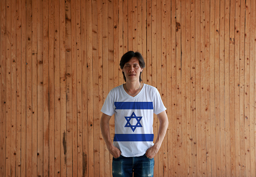 Man wearing Israel flag color shirt and standing with two hands in pant pockets on the wooden wall background.