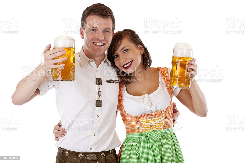man wearing lederhose and woman in dirndl with beer stein royalty-free stock photo