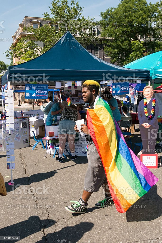 Man wearing LGBT flag before Hillary stand during Rockland Pride stock photo
