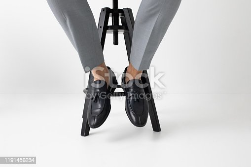 Legs of unrecognisable elegant man sitting on chair and wearing loafers.