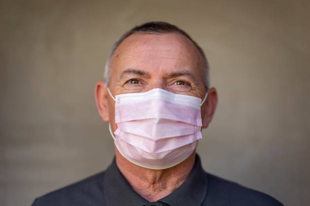 Man wearing mask as part of coronavirus spreading prevention campaign stock photo