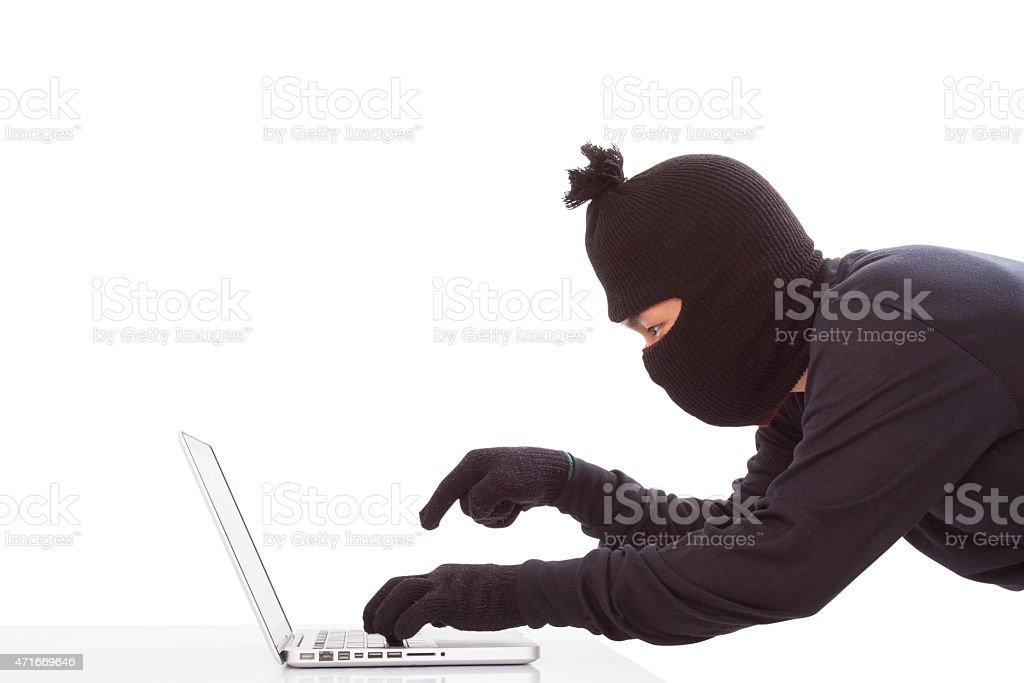 man wearing mask stealing data on laptop computer stock photo