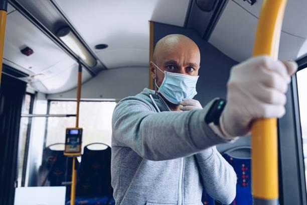 Mann mit medizinischer Maske und Schutzhandschuhen im Bus. Öffentliche Verkehrsmittel während covid-19 – Foto