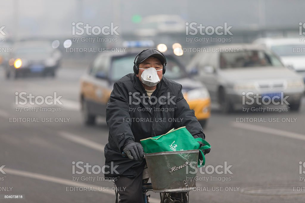 Man wearing mouth mask with filter against air pollution, Beijing stock photo