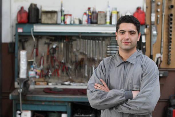 Macacão desgastando do homem em uma garagem com as ferramentas no fundo - foto de acervo