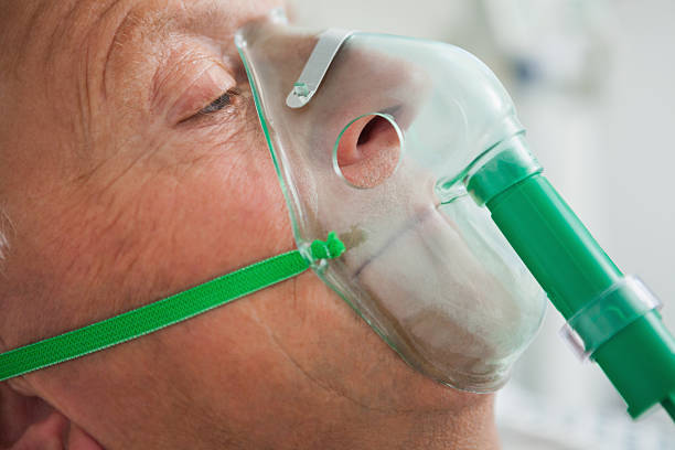 Man wearing oxygen mask Man wearing oxygen mask in hospital oxygen mask stock pictures, royalty-free photos & images