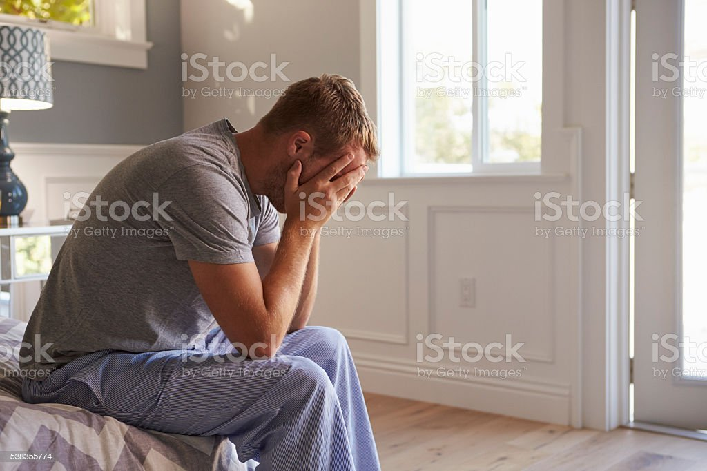 Man Wearing Pajamas Sitting On Bed With Head In Hands stock photo