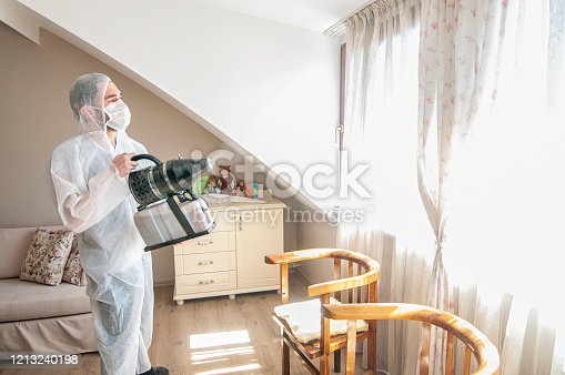 Medic sphysician scientist make disinfection and ventilation at living room