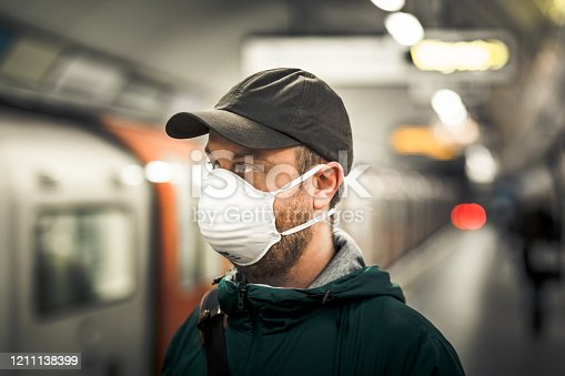 Close up color image depicting a young caucasian man in his 30s wearing a white protective face mask - to protect himself from flu viruses and the coronavirus - in an underground subway station in the city of London. He is wearing casual clothing, a green rainmack and olive green baseball cap, and is looking directly at the camera. In the background, a passenger train and people are defocused. Room for copy space.