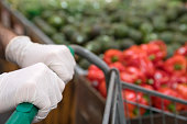 Man's hands, on shopping cart wearing gloves, for protection from infection.