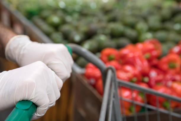 Mann mit Schutzhandschuhen beim Einkaufen im Supermarkt. – Foto