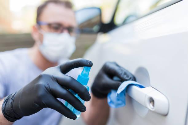 Hombre usando máscara protectora y guantes mientras usa un pequeño paño de microfibra y pulverizador de alcohol desinfectante para eliminar la suciedad o las bacterias de la manija de la puerta del coche. - foto de stock