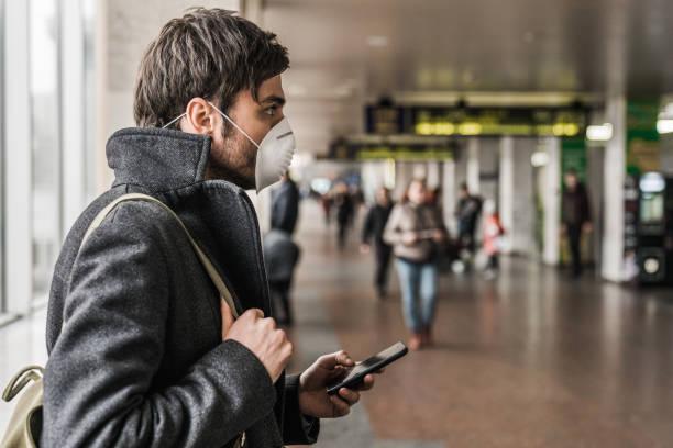 man wearing protective mask to prevent flu disease and coronavirus using mobile phone in airport terminal - covid flight imagens e fotografias de stock