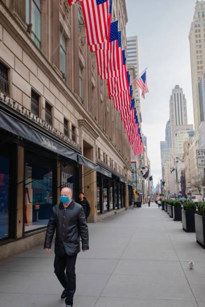 Mann mit Schutzmaske, der immer überfüllte Fifth Avenue hinuntergeht, ist wegen Coronavirus-Ausbruchs verlassen – Foto