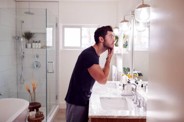 Man Wearing Pyjamas Standing At Sink Putting On Moisturizer In Bathroom stock photo