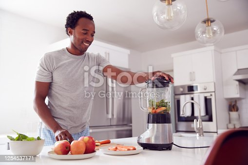 Man Wearing Pyjamas Standing In Kitchen Putting Fresh  Fruit And Vegetables Into Blender