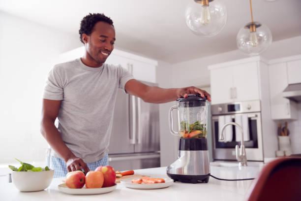 Man Wearing Pyjamas Standing In Kitchen Putting Fresh  Fruit And Vegetables Into Blender stock photo