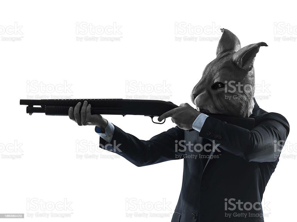 man wearing rabbit mask hunting with shotgun silhouette portrait royalty-free stock photo