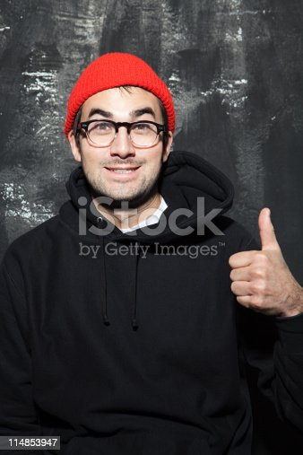 istock Man wearing red knit hat with thumbs up at party 114853947
