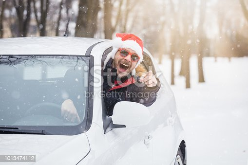 Portrait of car driver with santa hat through car window. On the road winter vacation and holidays concept.