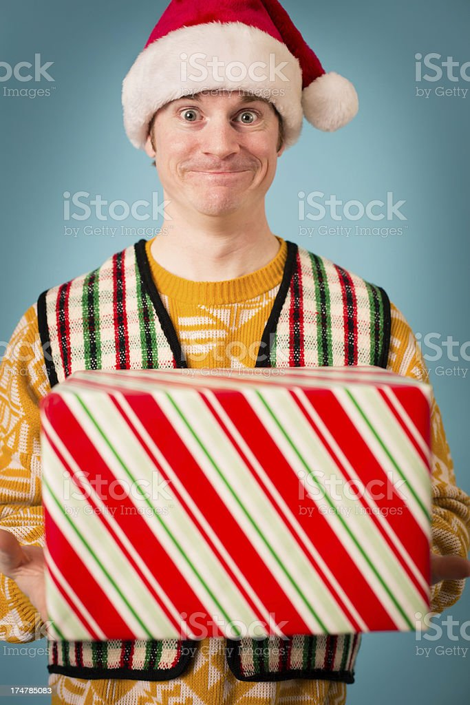 Man, Wearing Santa Hat and Ugly Sweater, Holding Gift royalty-free stock photo