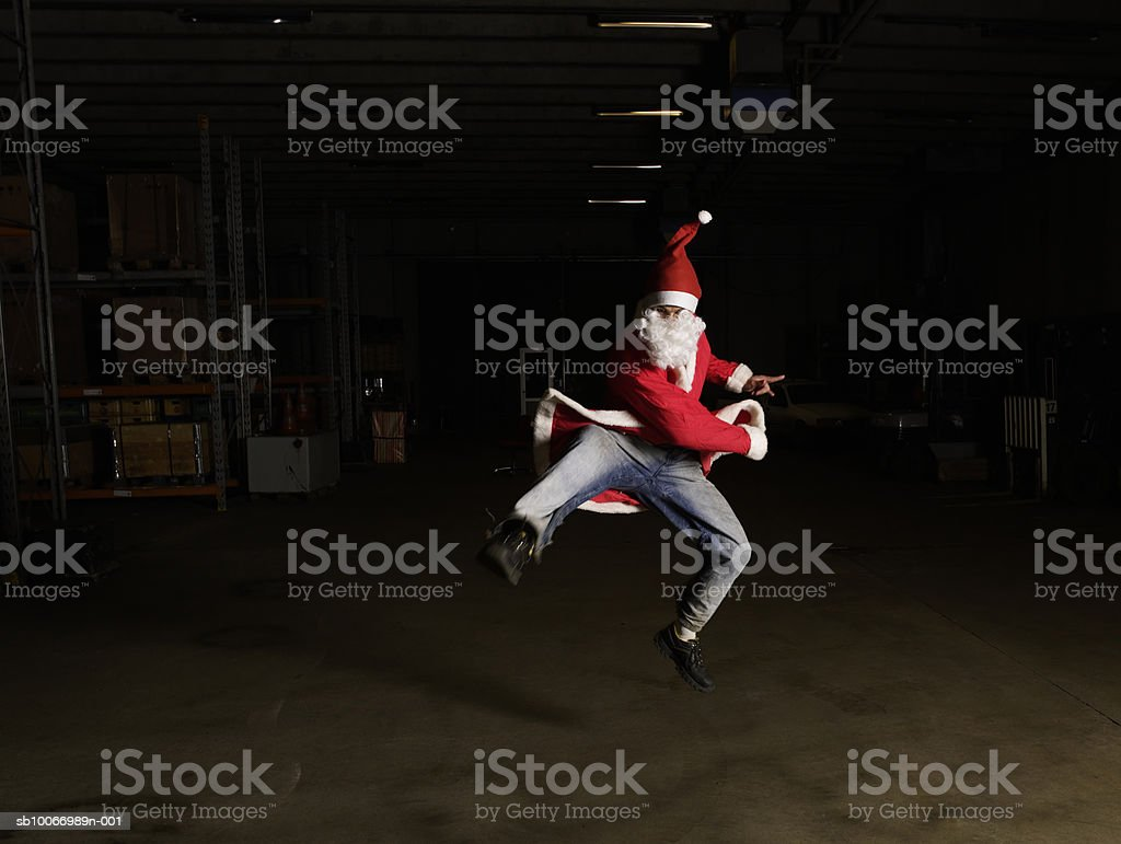 Man wearing santa outfit jumping in warehouse royalty-free stock photo