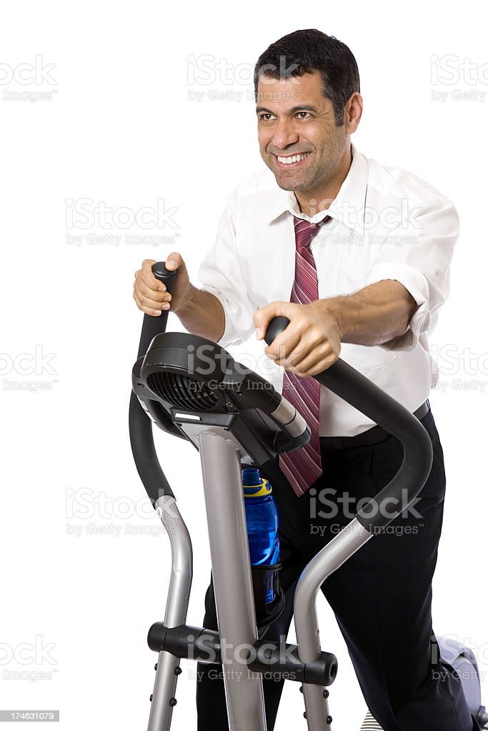 Man wearing shirt and tie on elliptical exercising royalty-free stock photo