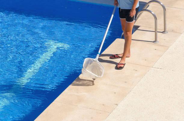 mann trägt shorts reinigt das schwimmbad mit einem netz - flip flops reparieren stock-fotos und bilder