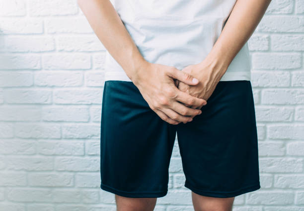 man wearing shorts holding genitals. Men's health, venereologist, sexual disease man wearing shorts holding genitals. Men's health, venereologist, sexual disease prostate gland stock pictures, royalty-free photos & images