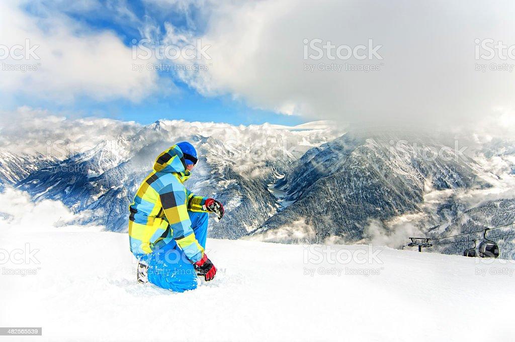 Man wearing ski equipment resting in mountain ski vacation stock photo