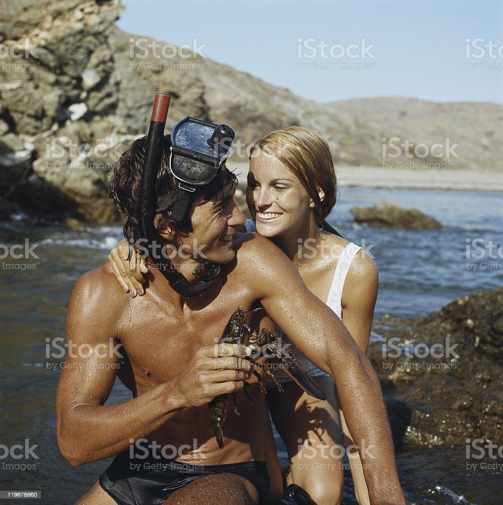 Man wearing snorkel, holding lobster beside woman, smiling stock photo