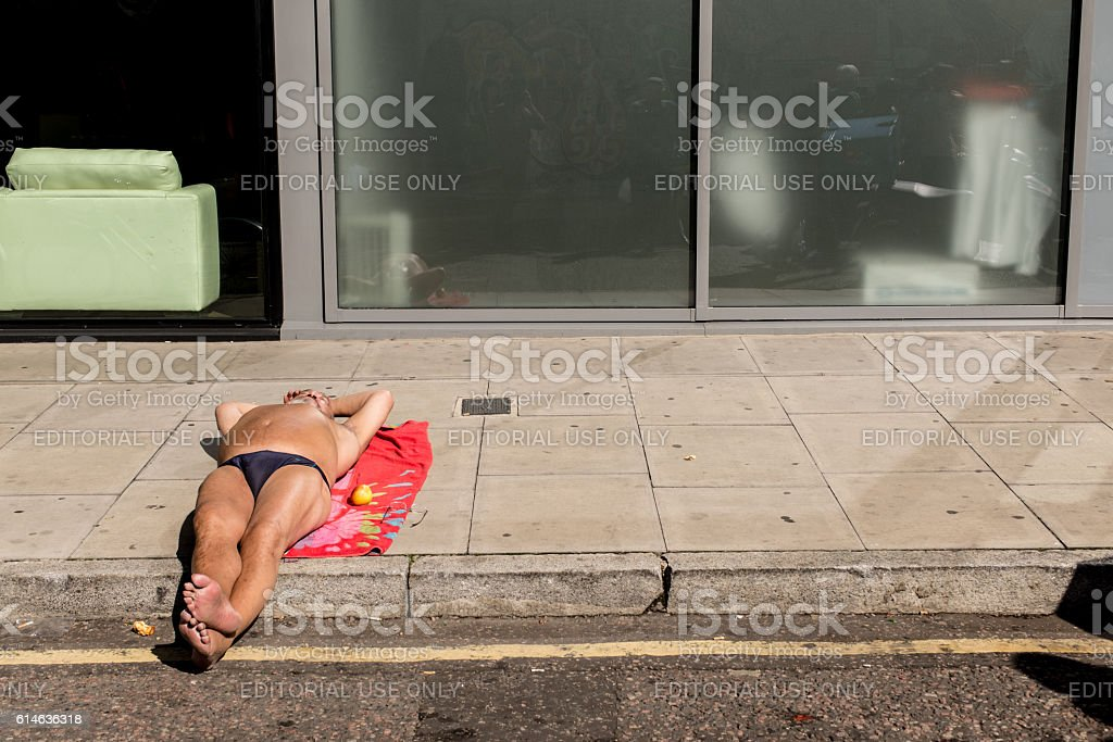 Man wearing speedos lying down and sunbathing on the pavement stock photo