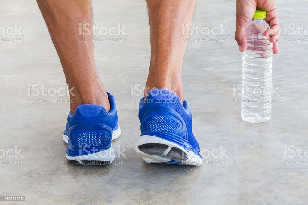 Man wearing sport shoes, picking up water bottle, sport concept foto stock royalty-free