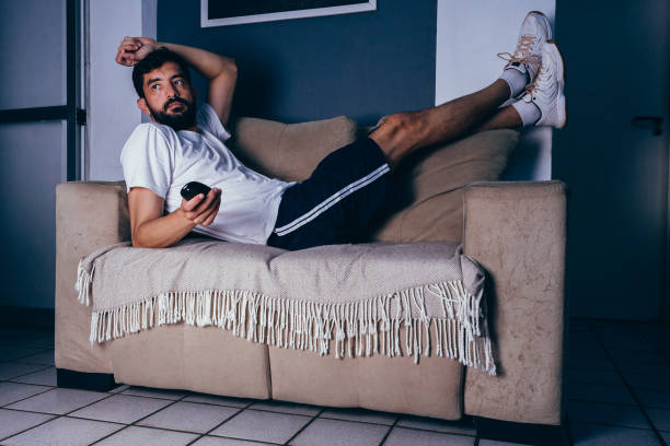 man wearing sportswear lying on the couch watching tv. laziness concept - sloth stock pictures, royalty-free photos & images